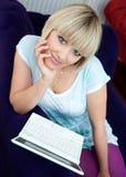 Kvinna med bärbar dator på sofaen royaltyfria foton