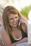 Kvinna med bärbara datorn genom att använda mobiltelefonen Fotografering för Bildbyråer