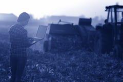 Kvinna med bärbara datorn i fältet royaltyfri bild