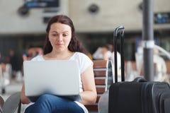 Kvinna med bärbara datorn i flygplats, genom att använda internetuppkoppling arkivfoto