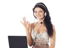 Kvinna med bärbara datorn och hörlurar med mikrofon som visar det ok tecknet Arkivfoto