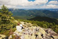Kvinna med bärbara datorn på berget Arkivbild