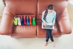 Kvinna med bärbara datorn som direktanslutet shoppar med debiteringkortet på soffan i hom Royaltyfria Foton