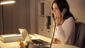 Kvinna med bärbara datorn som kallar på telefonen på nattkontoret arkivfilmer