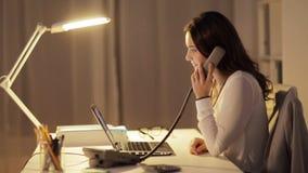 Kvinna med bärbara datorn som kallar på telefonen på nattkontoret lager videofilmer