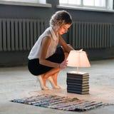 Kvinna med böcker och den ljusa ljusa kulan Royaltyfri Bild