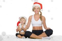 Kvinna med barnet som gör yoga i julhattar Arkivfoton