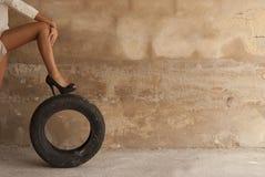 Kvinna med benet på gummihjulet Fotografering för Bildbyråer