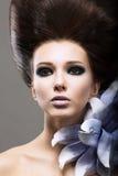 Elegans. Stående av den unga brunetten med blomman. Flott Coiffure och ljus Makeup Arkivfoto