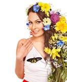Kvinna med blomman och fjärilen. Arkivfoto