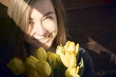 Kvinna med blommor i ett mörkt rum fotografering för bildbyråer
