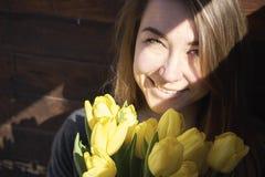 Kvinna med blommor i ett mörkt rum royaltyfria foton