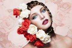 Kvinna med blommor i hår på blommabakgrund Royaltyfri Foto
