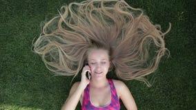 Kvinna med blont fantastiskt långt hår som ligger på gräs lager videofilmer