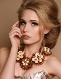 Kvinna med blont hår och ljus makeup med den lyxiga halsbandet arkivfoton