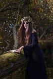 Kvinna med boken i mörk skog Arkivfoto