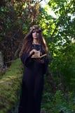 Kvinna med boken i mörk skog Royaltyfri Bild