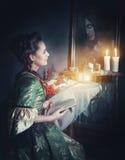 Kvinna med boken i retro klänning och spöke i spegeln Royaltyfri Bild