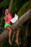 Kvinna med bärbara datorn som placeras i ett träd Arkivbilder