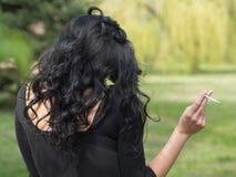 Kvinna med brinnande cigaretter Fotografering för Bildbyråer