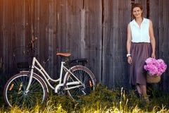 Kvinna med buketten av pioner och cykeln royaltyfria foton