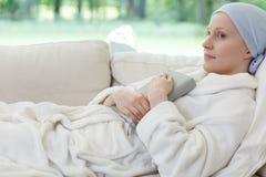Kvinna med cancer på soffan arkivbild
