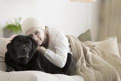 Kvinna med cancer som kramar hunden arkivbild