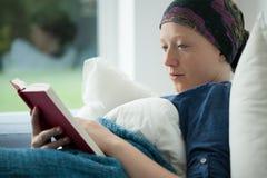 Kvinna med cancer som läser en bok Arkivfoton