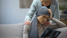 Kvinna med cancer som ser röntgenstrålen, stöttande dotter för moder, försämring stock video