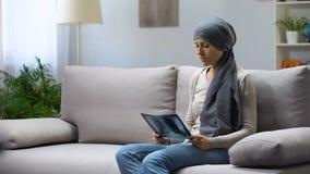 Kvinna med cancer som sitter på soffan och ser lungaröntgenstrålen som hoppas för att läka arkivfilmer