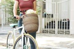 Kvinna med cykeln och korgen av mat royaltyfri foto