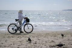 Kvinna med cykeln på stranden Royaltyfri Bild