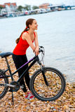 Kvinna med cykeln på stranden Arkivfoto