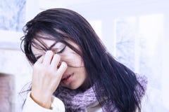 Kvinna med dålig huvudvärk i vinter Arkivbild