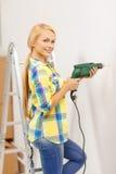 Kvinna med danandehålet för elektrisk drillborr i vägg Arkivbild
