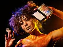 Kvinna med dekorativa skönhetsmedel Flickan rymmer den ögonskugga och borsten Arkivbild
