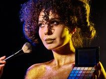 Kvinna med dekorativa skönhetsmedel Flickan rymmer den ögonskugga och borsten Arkivbilder