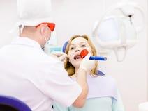 Kvinna med den öppna munnen som mottar tand- fyllnads- uttorkningproc Royaltyfria Bilder