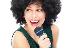 Kvinna med den afro frisyrinnehavmikrofonen Arkivfoton