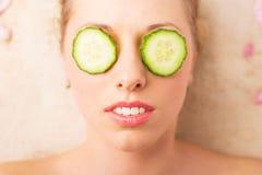 Kvinna med den ansikts- maskeringen av gurkaskivor på hennes ögon arkivbild