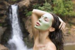 Kvinna med den ansikts- maskeringen för blå lera i (den utomhus-) skönhetbrunnsorten, Fotografering för Bildbyråer