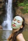 Kvinna med den ansikts- maskeringen för grön lera i (den utomhus-) skönhetbrunnsorten, Royaltyfri Bild