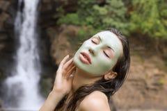 Kvinna med den ansikts- maskeringen för grön lera i (den utomhus-) skönhetbrunnsorten, Royaltyfria Bilder