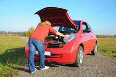 Kvinna med den brutna ner bilen Royaltyfri Bild