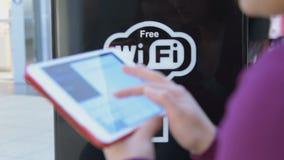 Kvinna med den digitala minnestavlan i fritt område Wi-Fi lager videofilmer