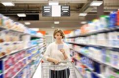 Kvinna med den driftiga vagnen för shoppinglista som ser gods i supermarket arkivfoton