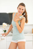 Kvinna med den elektriska tandborsten i badrum Royaltyfri Foto
