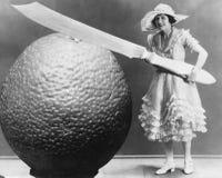 Kvinna med den enorma kniven och stycket av frukt (alla visade personer inte är längre uppehälle, och inget gods finns Leverantör arkivbild