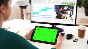 Kvinna med den gröna skärmen på minnestavlaPC hemma lager videofilmer