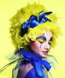 Kvinna med den gula perukfjädern Arkivbild